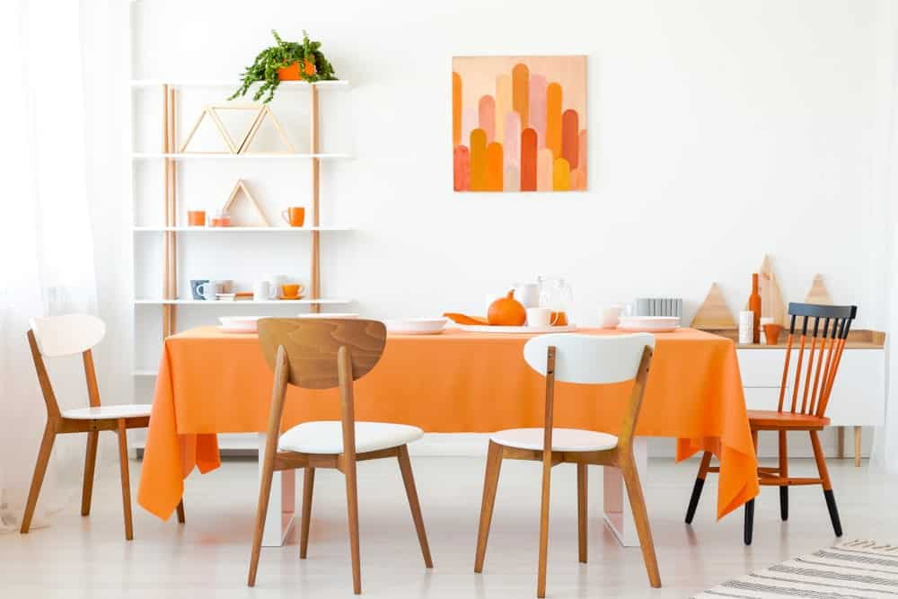 The stark white walls and flooring are a bright background that puts emphasis on the various orange elements scattered in this dining room like the table cloth, wall-mounted artwork, chair and ceramic wares in the background.