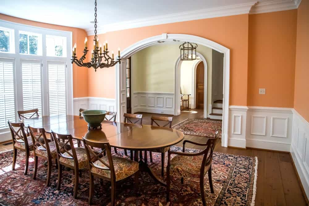 The beautiful orange walls of this formal dining room provides a quality of warmth to the sturdy white wainscoting and wooden dining set. This is augmented by the floral patterns on the area rug and the seat cushions.