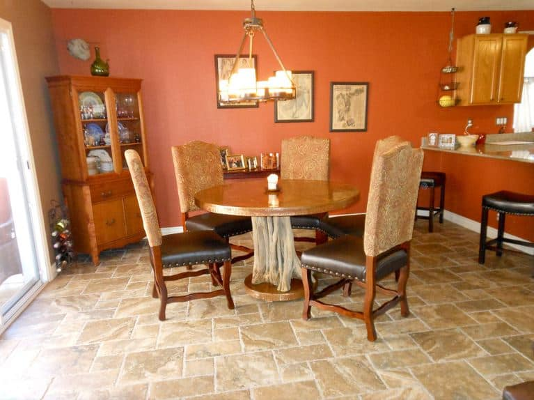 The rustic tree stump design of the wooden circular dining table is a match for the beige marble floors. This is the enhanced by the orange walls that have an earthy quality warmed up by the yellow lights of the chandelier.
