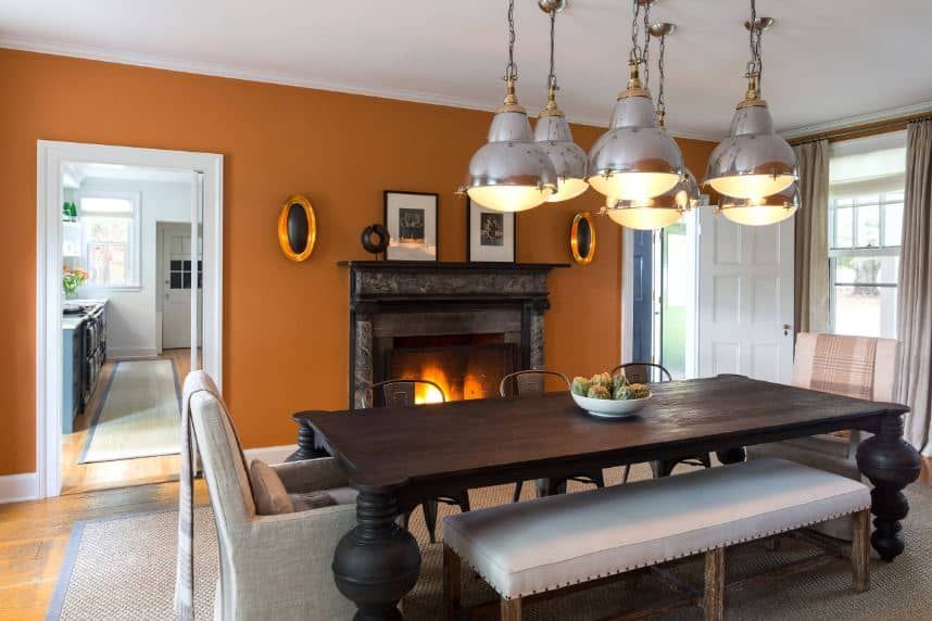 This dining room has a combinations of different elements that are bonded together by the warmth projected by the earthy orange walls and the fireplace on the side with a dark mantle that matches with the wooden table with peculiar legs matching with the modern pendant lights.