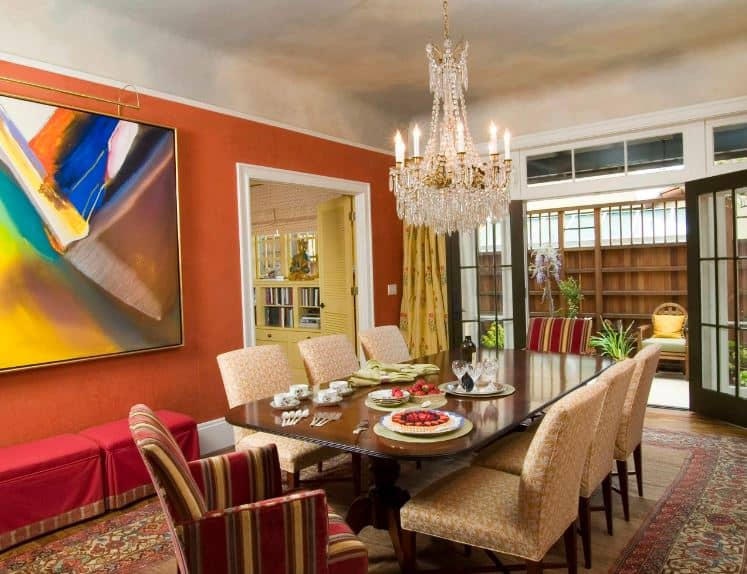 The colorful abstract painting provides a nice dash of color for the earthy walls of this dining room. This is augmented by a ceiling that looks like a cloudy sky with the lights coming from the crystal chandelier.