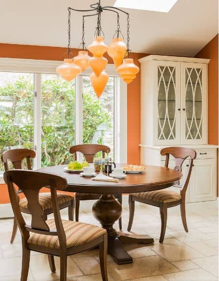 The wooden circular dining table and its matching wooden chairs have a chocolate brown hue to them that goes well with the orange elements that can be seen on the walls and the pendant lights that look like shells casting a warm yellow light.