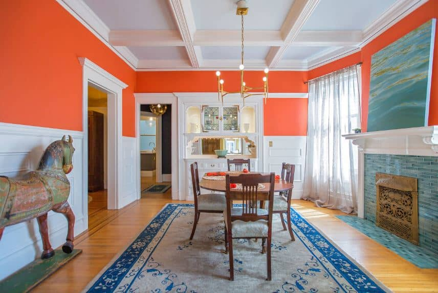 The orange upper walls of this dining room is paired with stark white wainscoting that brightens up the sea-green elements on the painting above the mantle of the fireplace that is inlaid with the same hue. This complements the blue patterned area rug over the hardwood flooring.
