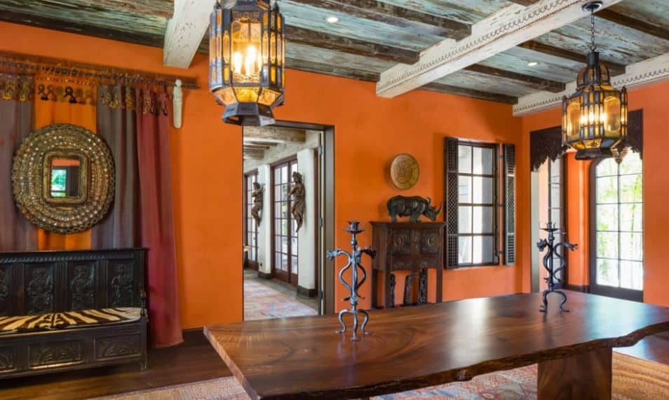 The wooden and earthy tribal decors of this dining room are amazing accents for the orange walls. These decors also match with the rustic wooden dining table and the hardwood flooring that is mostly covered by a colorful area rug.