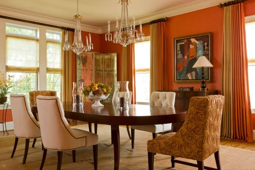 The large wooden dining table has rose patterned beige chairs on its heads while the rest are white cushioned. This is paired with tall orange walls with tall windows that has curtains of orange and beige to complete the aesthetic.