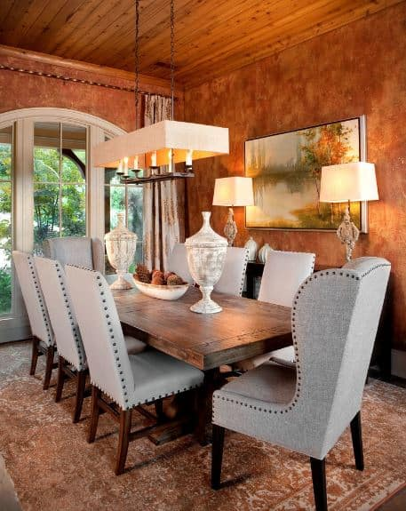 The rust-like shade of the orange walls is adorned with a colorful painting of a pond. This painting is flanked by table lamps on a console table beside the wooden dining table that is paired with gray cushioned dining chairs that stand out against the rust-colored area rug.