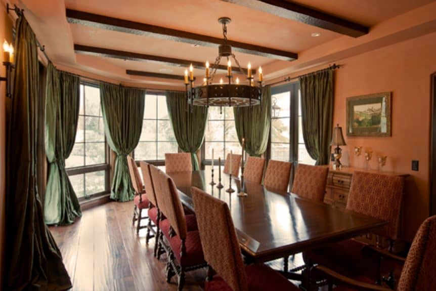 The curved far wall of this dining room is dominated by tall windows with lovely green curtains. These windows bring in an abundance of natural lights to the orange hue of the walls and ceiling with exposed wooden beams that match the wooden table.