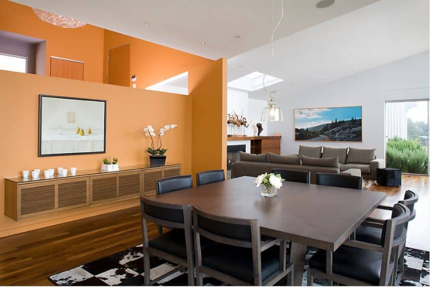 The square dining table has a dark gray tone matching the chairs surrounding it that has black leather cushions which matches with the patterned area rug underneath. This is softened by the cheerful demeanor of the orange wall and its decors.