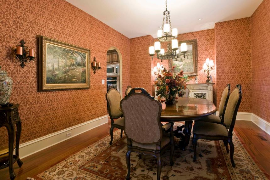 The elegantly patterned wallpaper of this dining room has an earthy shade of orange to it that complements the dark wooden table and its wooden chairs with gray cushions. These walls are adorned with a couple of colorful classic paintings that caps off the aesthetic.