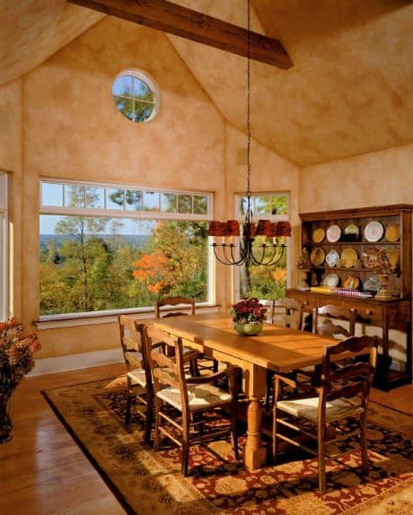 The sunset orange hue of the walls extends to the cathedral ceiling. This perfectly frames the lovely green scenery showcased by the wide windows bringing in natural lights to the wooden dining set over a colorful patterned area rug.