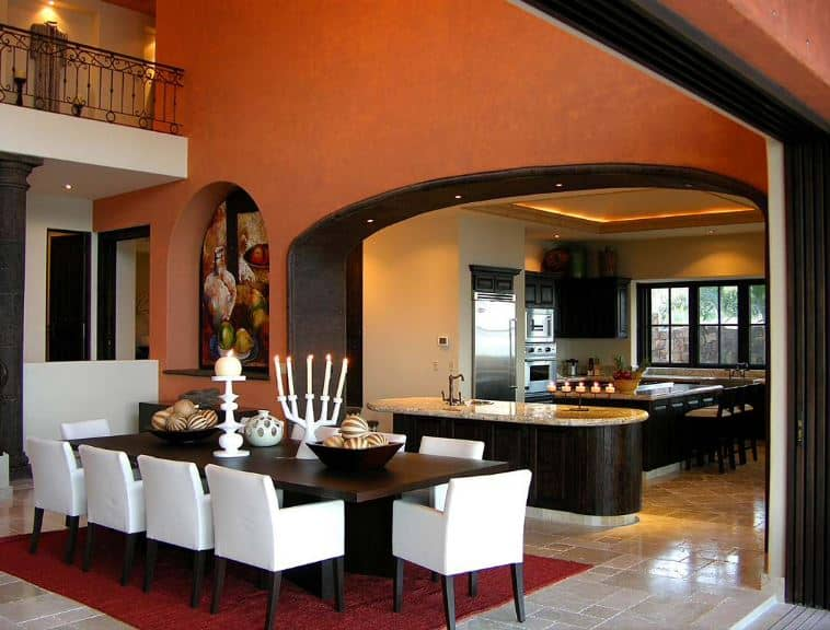 The kitchen and the dining area are separated by an arched entryway with a dark brown finish on it that matches with the wooden dining table. This is contrasted by the white cushions of the chairs and the decors on top. This contrast is softened by the earthy orange walls.