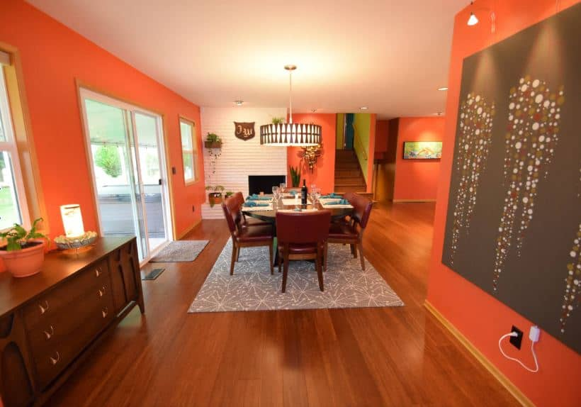 The cheerful orange walls of this dining area are a great compliment to the hardwood flooring that matches with the wooden hues of the dining set over the gray patterned area rug and under a modern circular pendant light.