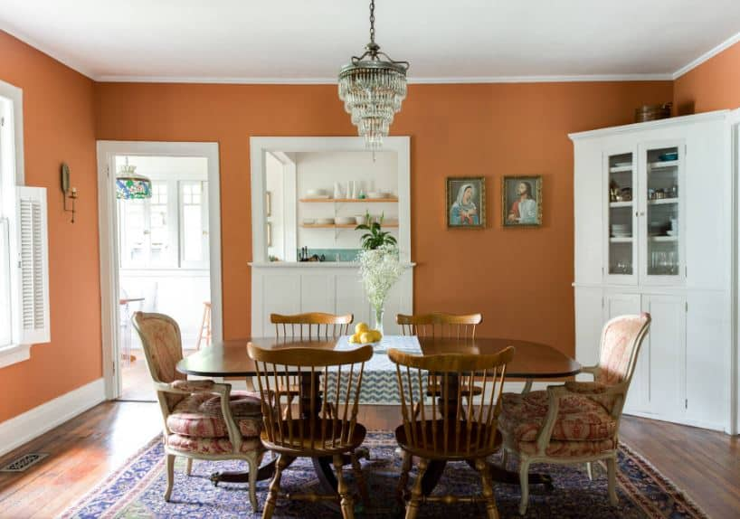 The earthy orange tone of the walls are contrasted by the white moldings that blend with the dining room corner cabinet, door frame and window frame. This is a nice background for the wooden dining table and slat back chairs over the colorful patterned area rug.