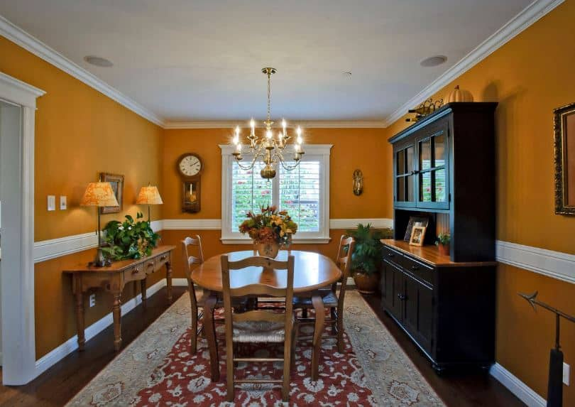 The black wooden dining room cabinet stands out against the earthy orange shade of the walls with white molding that matches with the white frames of the shuttered windows and ceiling that hangs a chandelier over the wooden dining set.