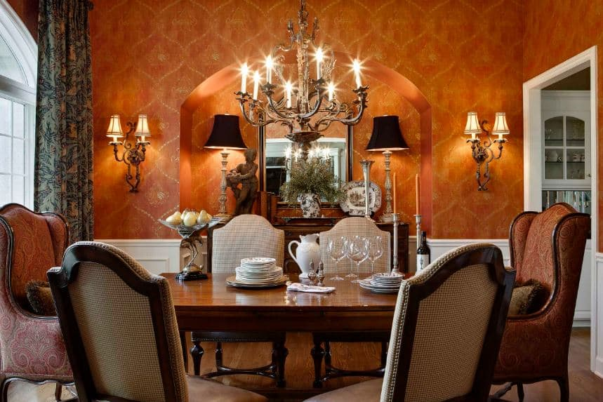 The patterned orange wallpaper is augmented by the warm yellow lights of the wall-mounted lamps that match with the elegance of the wrought iron chandelier hanging over the wooden dining table surrounded by cushioned chairs.