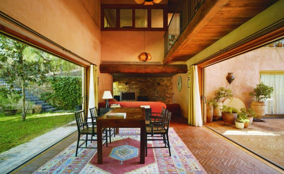 This delightful dining room has two walls that open up to the outside of the house that showcases two different but equally amazing landscaping. This provides a great background for the dining area that has orange walls and terracotta flooring covered with a colorful area rug contrasting the dining set.