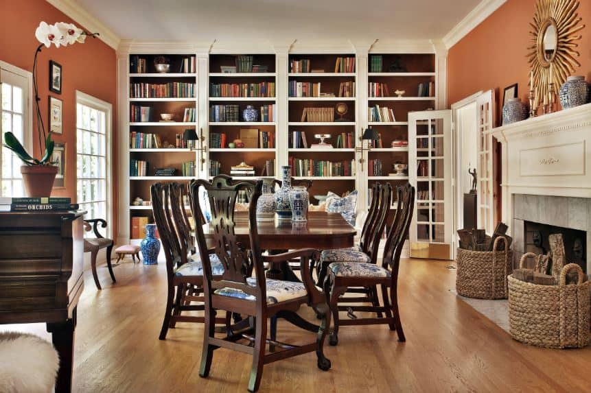 There is a large wall dominated by bookshelves on the far wall creating a warm and comfortable background for the wooden dining table and its dark wooden chairs with bright patterned cushions on the seats. Warmth is provided by the fireplace on the side with a white mantle that stands out against the orange walls.