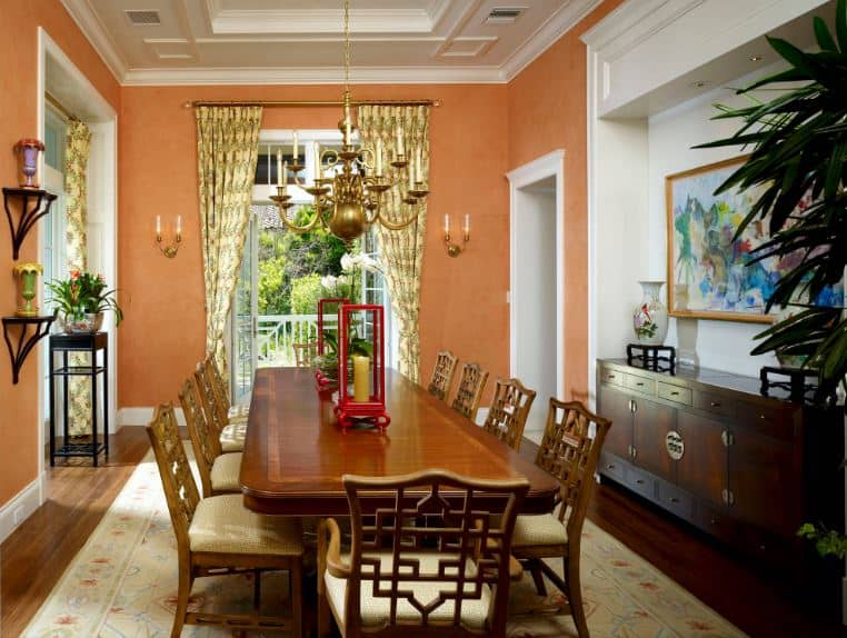 The earthy hue of the walls are easy on the eyes. They complement everything in this formal dining room like the wooden elements of the dining set with chairs that have oriental designs on their backs. These are all brightened by the white tray ceiling.