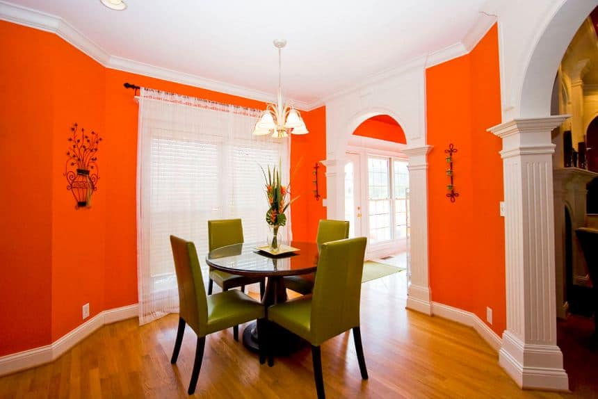The bright orange walls appear to be glowing with the addition of natural lights coming in from the curtained tall windows. All of these makes the avocado green leather chairs stand out as they encircle the round glass-top dining table.