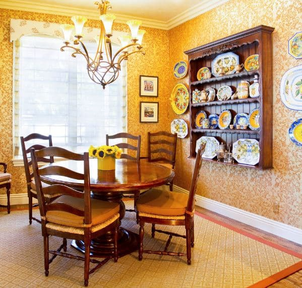 The orange wallpaper dominating the walls has subtle and complex patterns to it that elevates the elegance of the wooden dining set. This is balanced by the charming plate decors on the walls and on the wooden shelves.