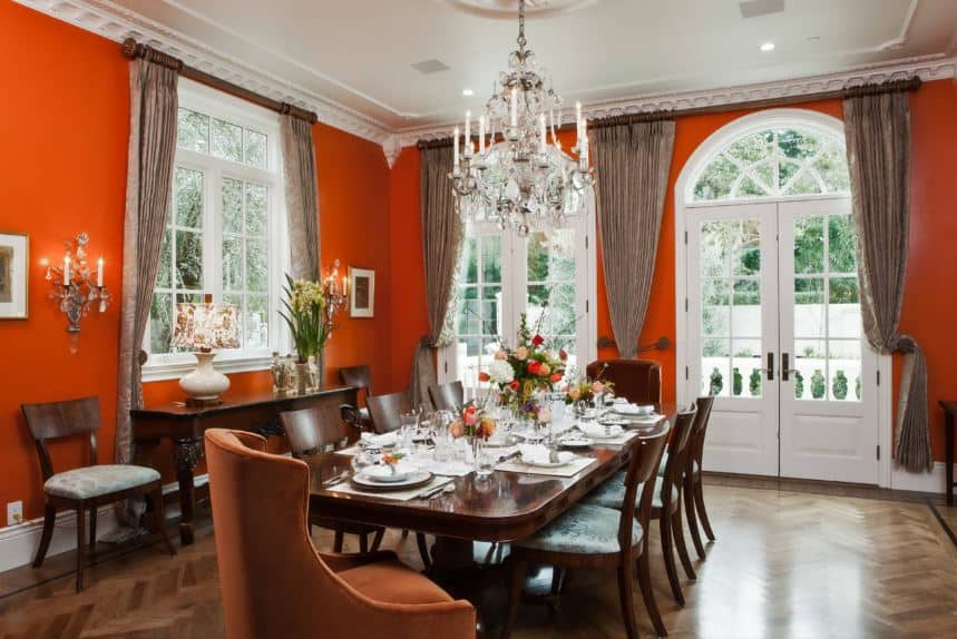 The tall windows and French glass windows and doors that are flanked with brown curtains have white frames that stand out against the red-orange walls adorned with wall lamps that match with the chandelier hanging from the white ceiling.