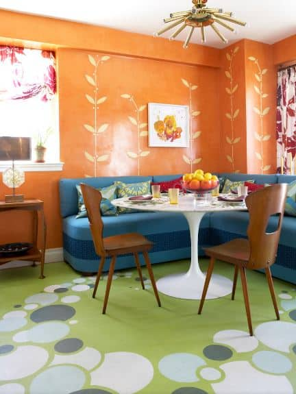 The lovely orange walls of this informal dining area has leafy vines drawn on them that makes it look like its growing from the L-shaped blue cushioned bench facing a modern white circular table and a pair of wooden chairs over a large green patterned area rug.