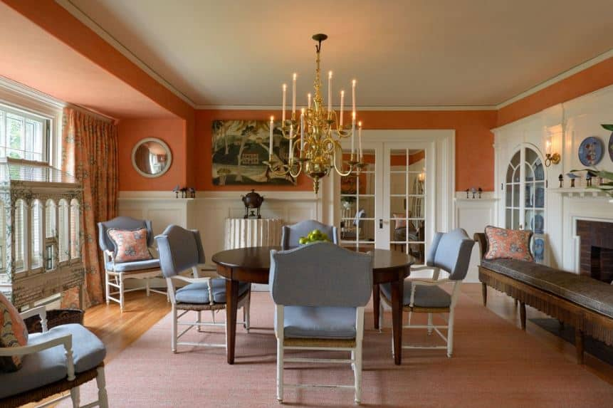 The multi-tier golden chandelier stands out in this room that has light blue chair cushions that surrounds a dark wooden table that stands out against the pink area rug over the hardwood flooring that is complemented by delightful orange walls.
