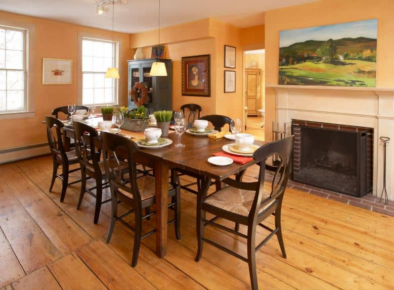 The colorful painting of a grassy meadow is a perfect fit for the sun-colored orange walls that bring a cheerful contrast for the dark wooden dining table and its dark wooden chairs that complement the hardwood flooring by the fireplace.