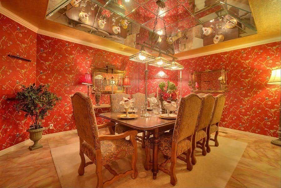 The red orange wallpaper of this dining room has charming flowers and vines forming a pattern that provides a complex and colorful background for the bare wooden flooring that matches with the wooden dining table and wooden chairs.