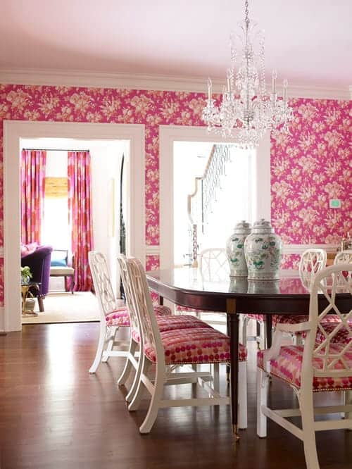 Charming dining room clad in pink floral wallpaper that complements with the white cushioned chairs surrounding a wooden oval table topped with a pair of jars.