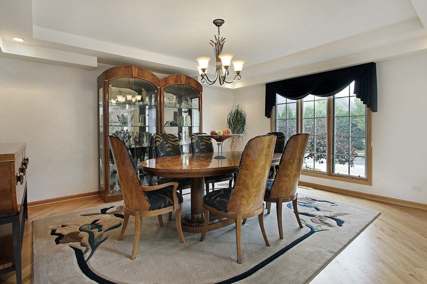 A pair of full glass display cabinets face the classy dining set in this white dining room with a vintage chandelier and a beige printed area rug that lays on light hardwood flooring.