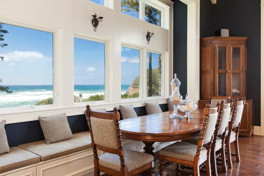 A serene dining room boasts a wooden dining set that blends in with the wood plank flooring along with a built-in bench underneath the glass paneled windows overlooking a breathtaking beach view.