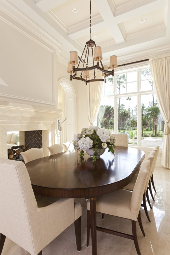Natural light streams in through the full height windows in this white dining room with upholstered dining chairs and dark wood oval table lighted by a chandelier that hung from the coffered ceiling.