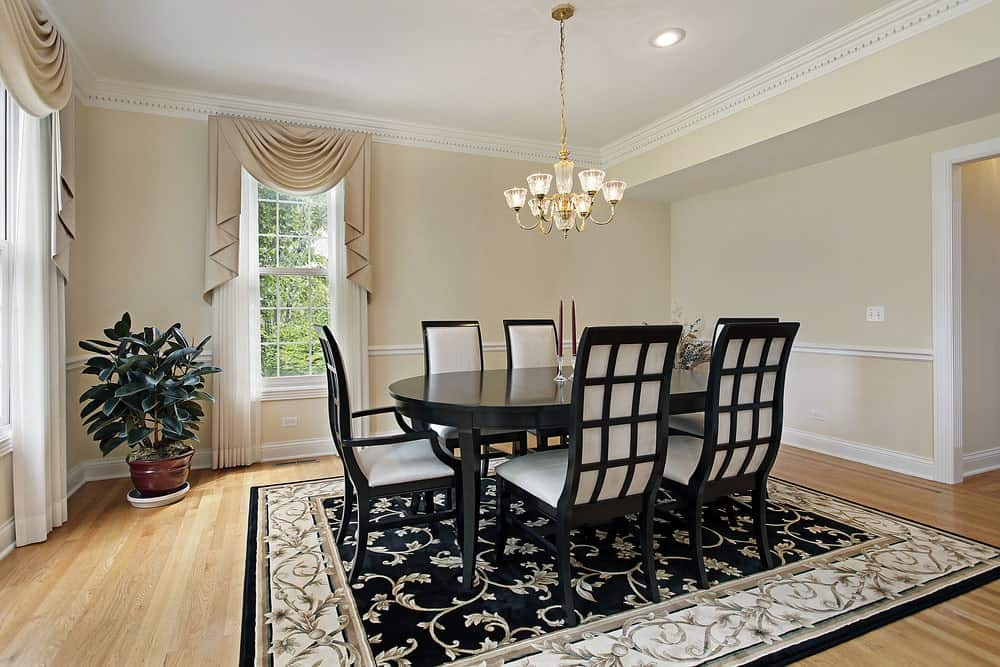 Sophisticated dining room with light hardwood flooring and white framed windows dressed in classy valances. It includes a brass chandelier and a black and white dining set that complements with the floral area rug.