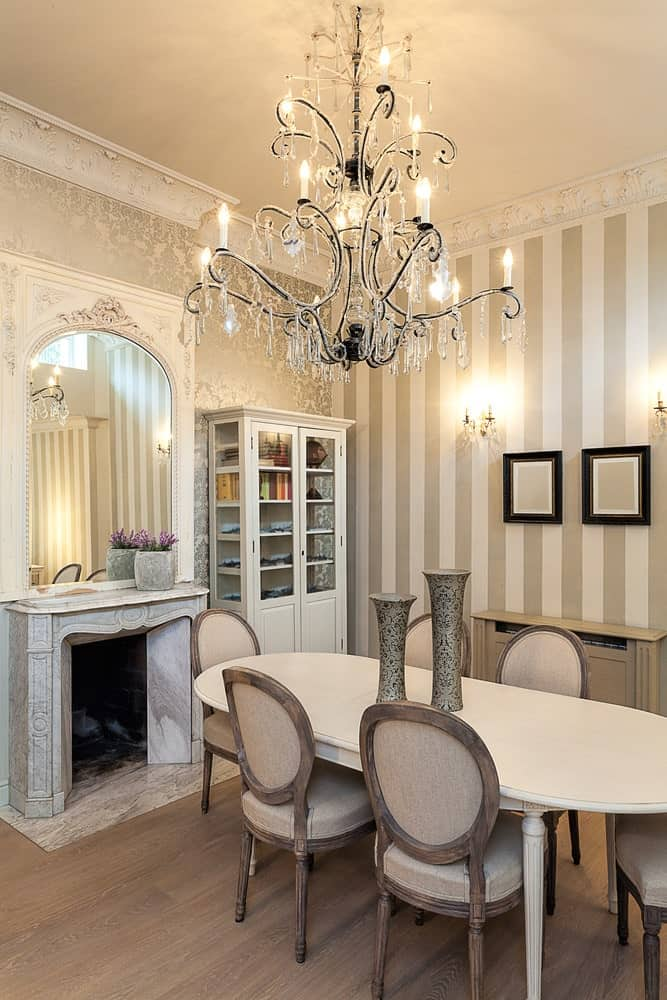 A large crystal chandelier hangs over the white oval table and round back dining chairs in this elegant dining room with a fireplace and display cabinet placed against the silver floral and striped wallpapers.