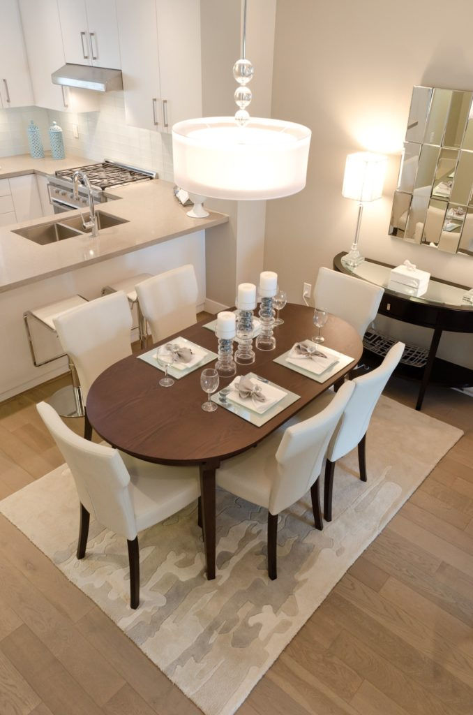 A modern dining area boasts a wooden oval table and white wingback chairs over a camo area rug lighted by a glass drum pendant. It is accompanied by a stylish mirror and dark wood console table topped with a glass lampshade.