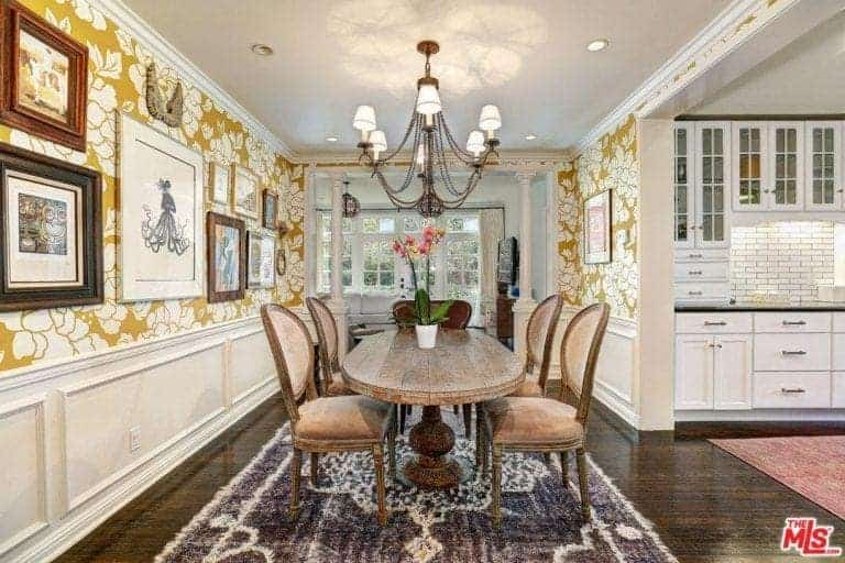 Charming dining room clad in white wainscoting and yellow floral wallpaper that's accented with gallery frames. It has a rustic oval table and brown velvet chairs lighted by a vintage chandelier.
