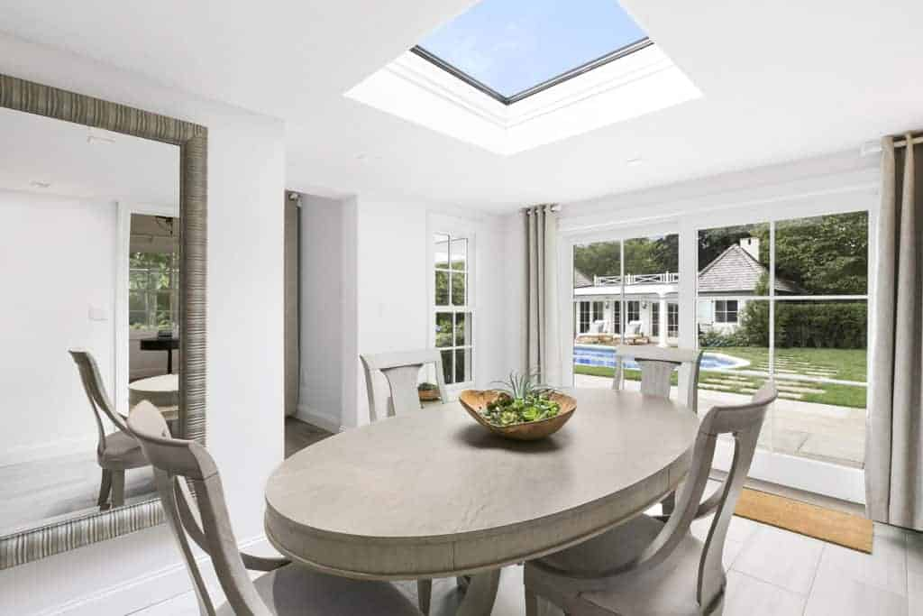 Minimalist dining room boasts a light wood dining set placed underneath the skylight and a full-height mirror that creates a larger visual space in the area.