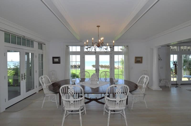 White dining room with light wood plank flooring and a French door that leads out to the lush green yard with a stunning beach view. It has white chairs and an oval dining table lighted by a candle chandelier.
