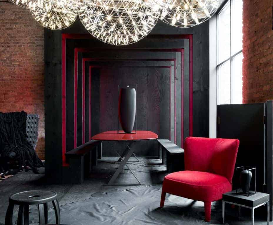 A red velvet chair and oval dining table add a pop of color to this black dining room showcasing round clustered pendants and cozy black seats that blend in with the wall and floor.