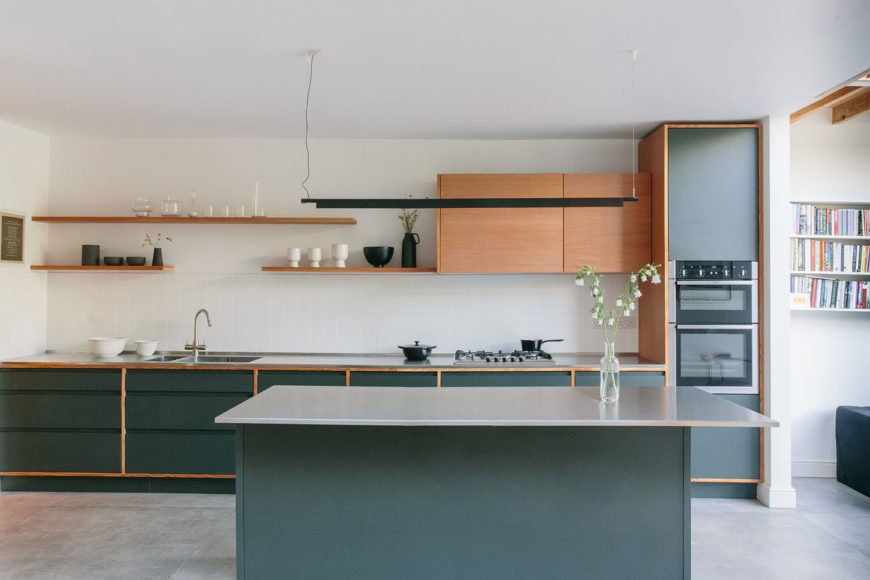 Modern bespoke kitchen with dark green cabinet doors in a douglas fir frame, douglas fir floating shelves and wall units, stainless steel worktop, and concrete tiles.