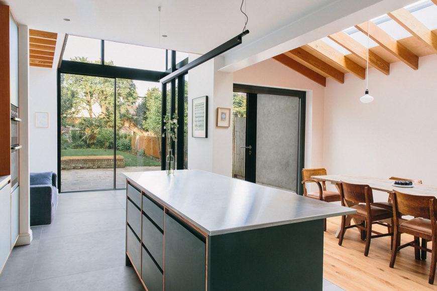 Modern kitchen island with stainless steel worktop and dark green cabinets.
