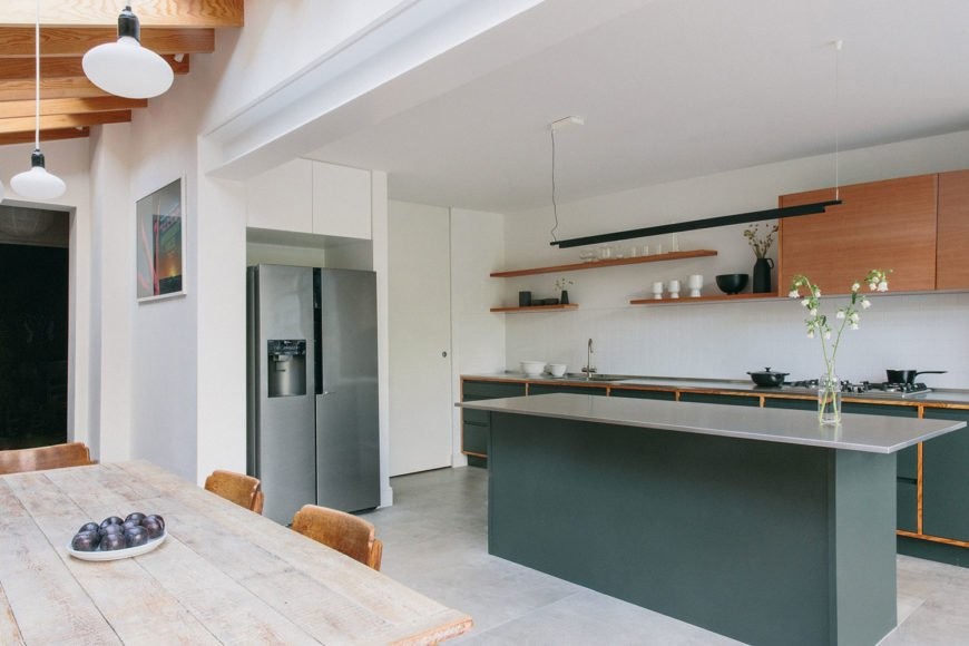 View from the rustic dining table of the kitchen with shaker dark green cabinets.