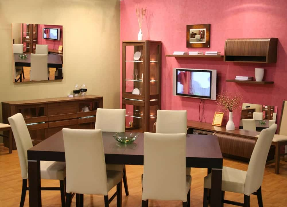 This is a delightful dining area that is adorned with a pink wall that serves as a background for the wooden glass cabinet and the entertainment set. This can be enjoyed by those on the dining set of wooden rectangular table and beige cushioned chairs.