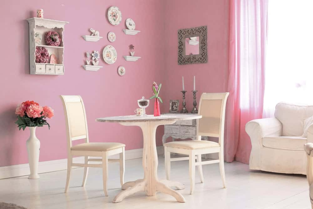 This bright and relaxing dining area is near a corner of cheerful baby pink walls that are accented with light-hued decors that stand out. This is perfectly paired with a rustic white wooden circular table paired with white wooden chairs.