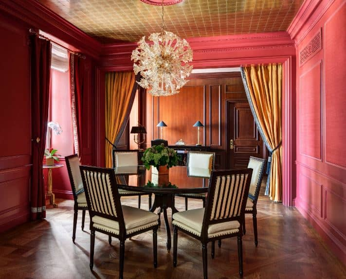 A brilliant sun-like crystal pendant light hangs over the circular dark wooden dining table and its dark wooden chairs with beige leather cushions. These stand out against the hardwood flooring that complements the pink walls with an elegant finish.