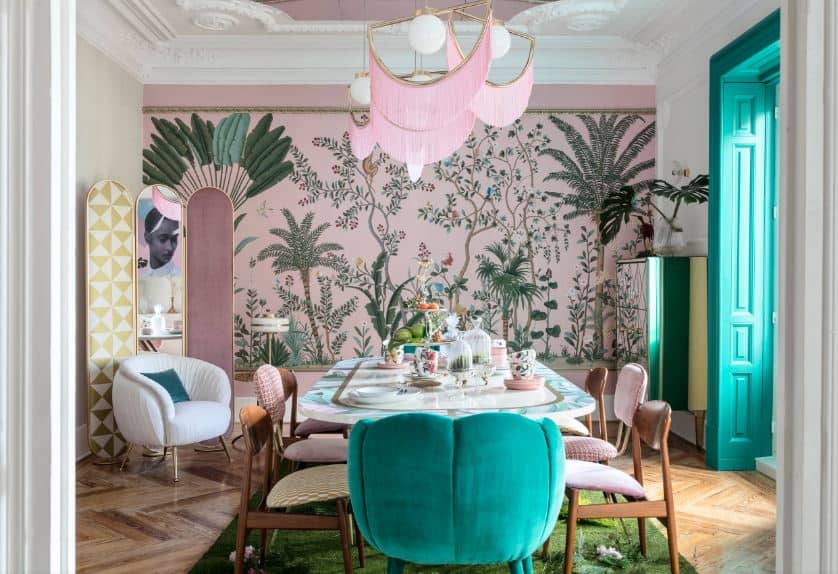 The lovely pink wall behind the head of the dining table is filled with a mural of trees and flowering plants that provide a nice complex background for the dining set that has a variety of chairs for that informal and quirky aesthetic.