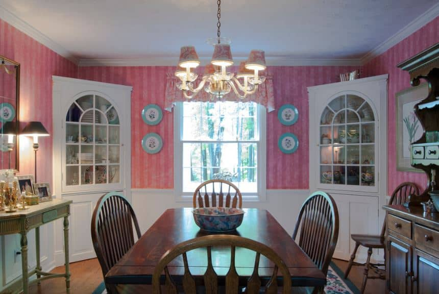 The are two white wooden corner cabinets that stand out against the delightfully chic pink patterned wallpaper that matches with the beautiful colorful design of the chandelier. These are contrasted by the dark wooden dining table and slat back chairs.