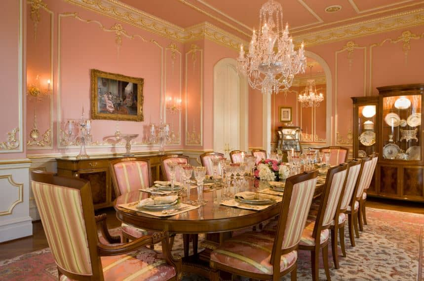 The salmon pink hue elevates the classic style of this elegant formal dining room. It gives accent to the walls that have a finish trimmed with gold matching with the pink ceiling that supports a majestic crystal chandelier.