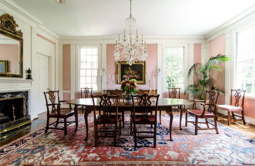 The hardwood flooring of this large and elegant dining room is dominated by the colorful patterned area rug that provides a colorful background for the wooden dining set. This is augmented by the salmon pink walls adorned with a classic painting and a mirror over the fireplace.